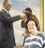 Sabiha accanto ad un quadro che la ritrae mentre bacia la mano del presidente in segno di rispetto e devozione